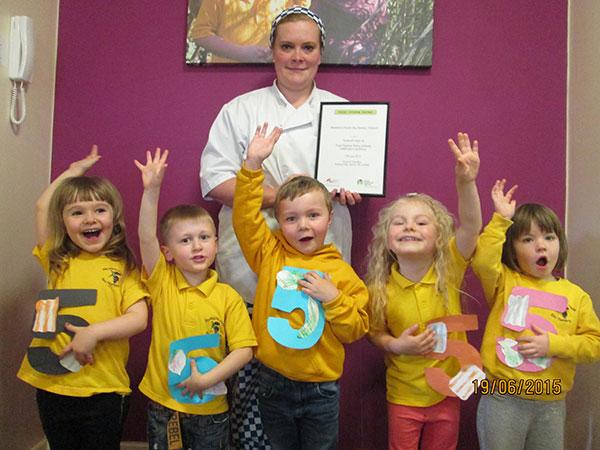 adult, 5 children holding 5s